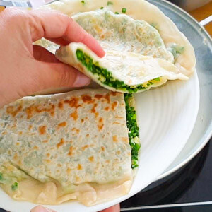 The tender green filling and the crispy wrapper of a Chinese chive and egg pocket